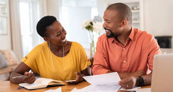 Mature African American couple sitting at the kitchen table discussing finances.