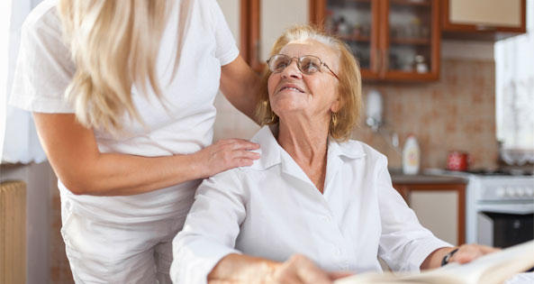 Young woman providing care and support to an older woman.